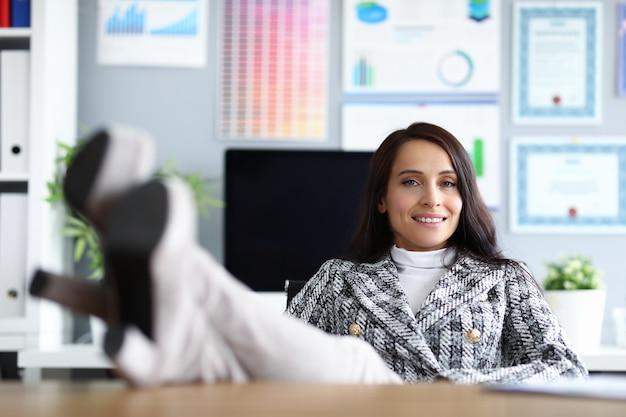 La donna in ufficio ha messo i piedi sul tavolo e sorride.