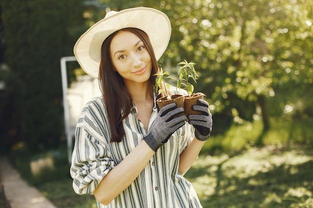 La donna in un cappello che tiene i vasi da fiori