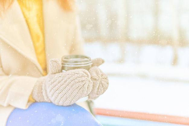 La donna in un cappotto beige, maglione giallo, pantaloni blu, guanti caldi beve caffè caldo per andare