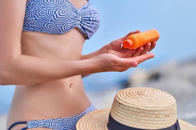 La donna in un costume da bagno tiene la bottiglia della protezione solare durante il sole al mare in tempo soleggiato in estate