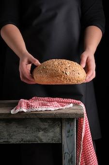 La donna in un grembiule nero tiene in sue mani al forno il pane di segale rotondo