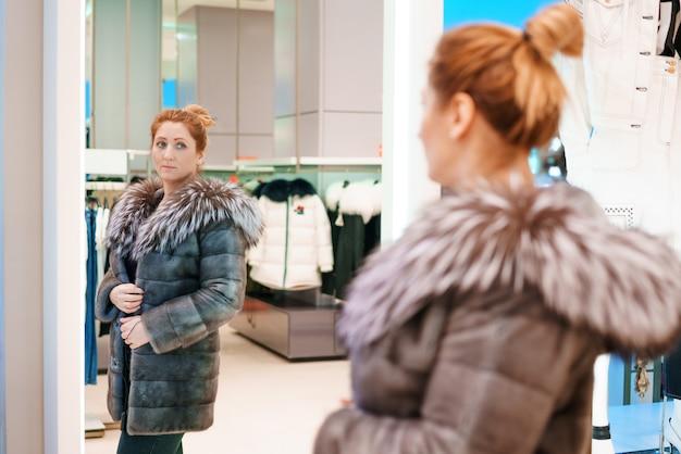 La donna in un negozio sceglie una giacca invernale