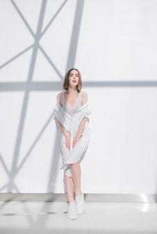 La donna in un vestito bianco alla moda propone sulla macchina fotografica all'interno su una priorità bassa astratta bianca