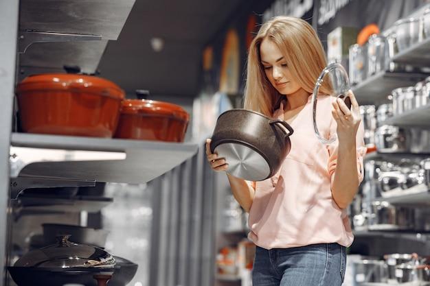 La donna in una camicetta rosa compra i piatti nel negozio