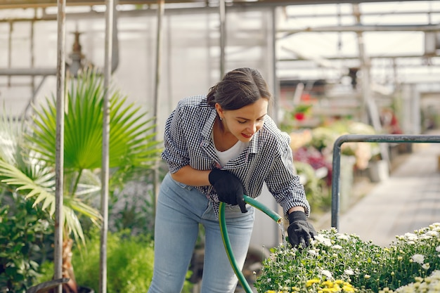 La donna in una camicia blu versa i vasi da fiori