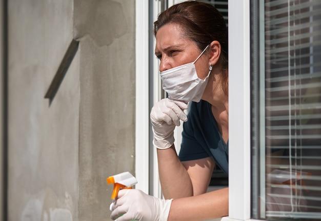 La donna in una mascherina medica osserva dalla finestra.