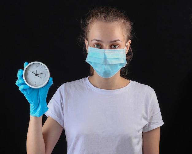 La donna in una mascherina protettiva medica, guanti tiene l'orologio bianco su una parete nera.