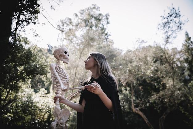 La donna in vestiti dello stregone che sembra attento allo scheletro
