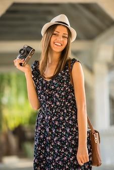 La donna in vestito e cappello sta tenendo la macchina fotografica antiquata.
