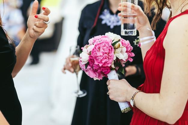 La donna in vestito rosso tiene un vetro mentre parla con la gente