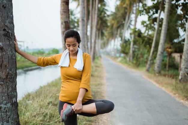 La donna incinta allunga la gamba durante l'esercizio all'aperto