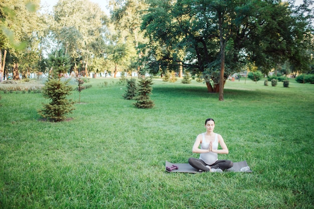 La donna incinta calma e pacifica si siede nella posa del loto in parco fuori da solo. si tiene per mano in posizione di preghiera. il modello sembra calmo e pacifico.