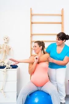 La donna incinta fa esercizi di stretching con fisioterapista