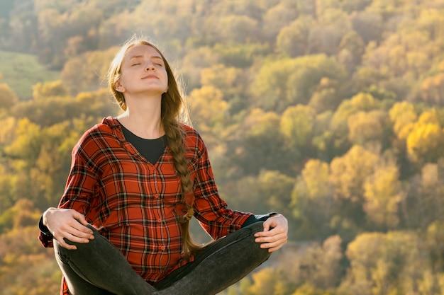 La donna incinta si siede su una collina con gli occhi chiusi. meditazione. foresta d'autunno