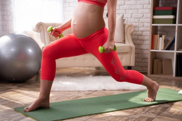 La donna incinta si sta allenando con i manubri.