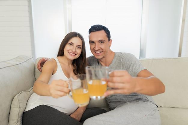 La donna incinta si trova sul divano. l'uomo è seduto accanto a lei.