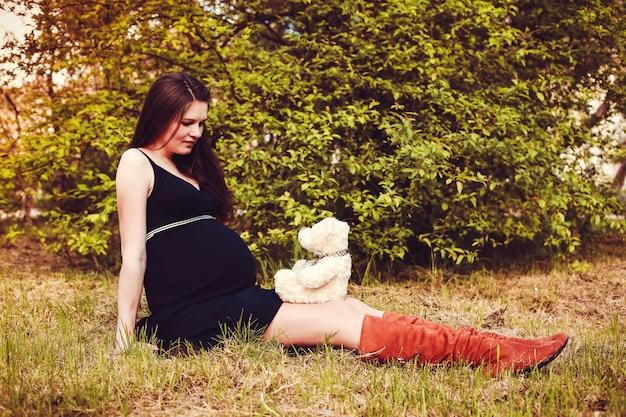 La donna incinta sta accanto al tramonto nel giardino