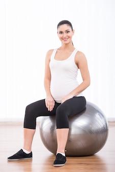 La donna incinta sta facendo esercizi con palla ginnastica.