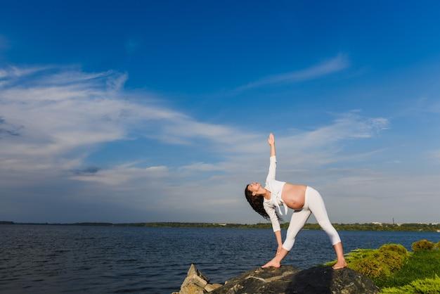 La donna incinta sta praticando yoga accanto al fiume
