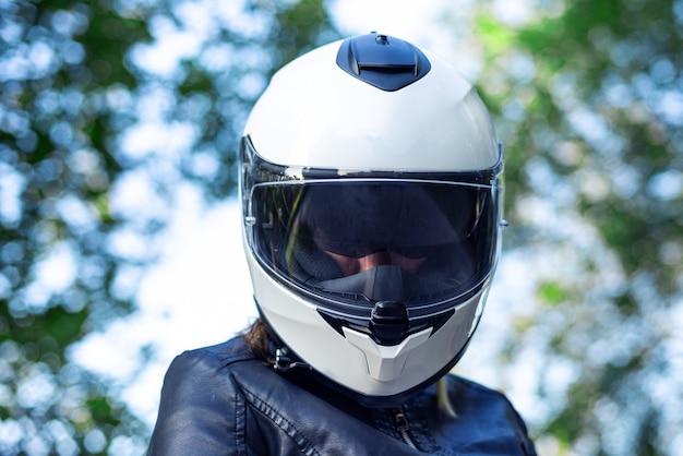 La donna indossa il casco da motociclista e allaccia la chiusura