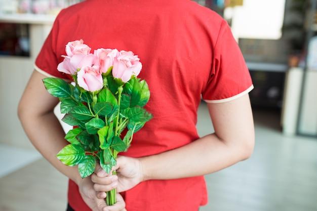 La donna indossa la camicia rossa che nasconde il mazzo della rosa di rosa sulla parte posteriore, concetto di san valentino