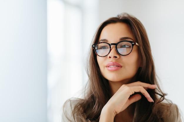 La donna indossa occhiali da vista con montature scure, tocca delicatamente il mento,