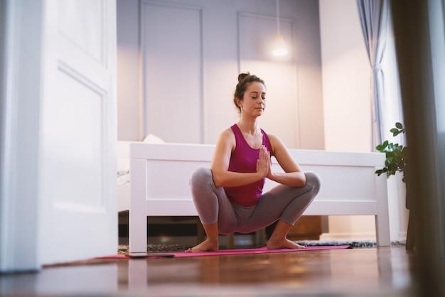 La donna invecchiata centrale sportiva di forma attraente che fa l'yoga seduta posa sul pavimento prima del sonno.