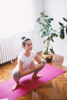 La donna invecchiata centrale sportiva di forma attraente che fa l'yoga seduta posa sul pavimento