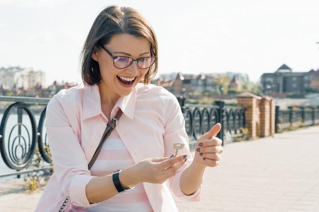 La donna invecchiata mezzo felice di affari nella tenuta della via digita la sua mano.