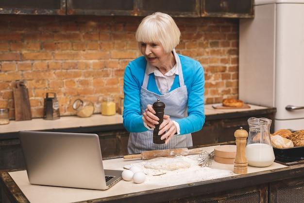 La donna invecchiata senior attraente sta cucinando sulla cucina. nonna che produce una cottura saporita. usando il laptop.