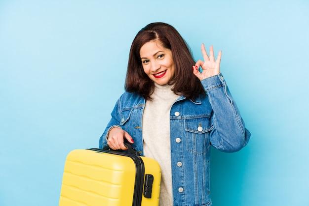 La donna latina del viaggiatore di età di middlr che tiene una valigia ha isolato il gesto giusto di mostra allegro e sicuro.