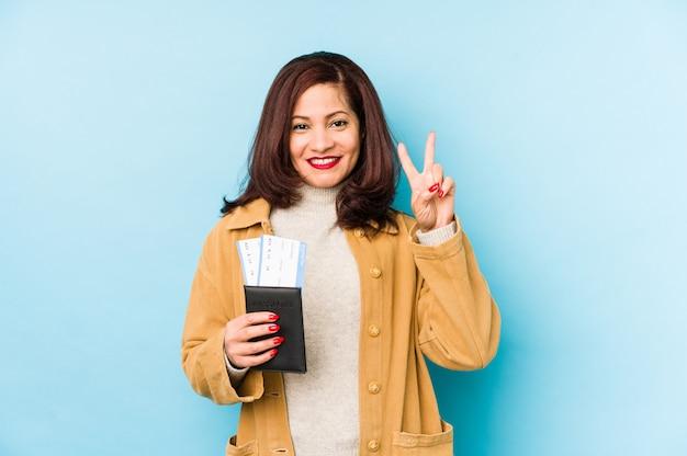 La donna latina di medio evo che giudica un passaporto ha isolato la mostra del numero due con le dita.