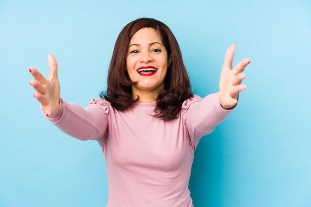 La donna latina di mezza età isolata si sente sicura dando un abbraccio alla macchina fotografica.
