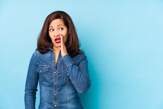 La donna latina di mezza età isolata su una parete blu sta dicendo una notizia di frenata calda segreta e sta guardando da parte
