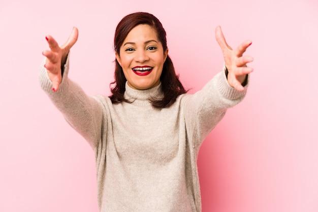 La donna latina di mezza età isolata su una parete rosa si sente sicura dando un abbraccio alla macchina fotografica.