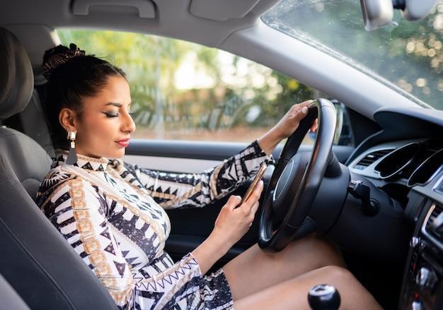La donna latina nell'abitacolo dell'auto guida e usa il suo smartphone