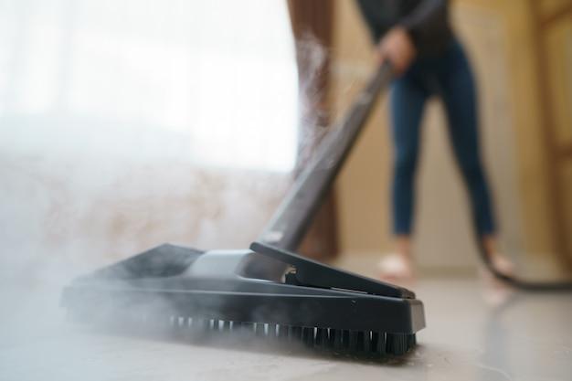 La donna lava il pavimento con una scopa a vapore.
