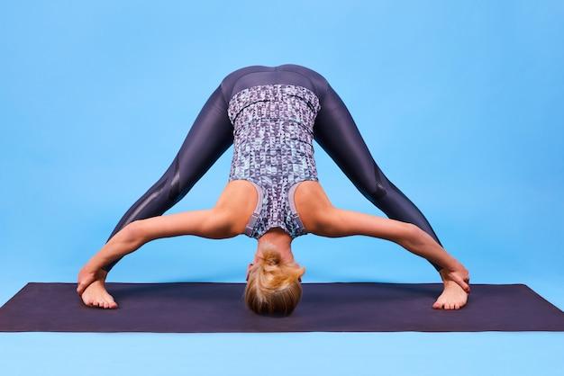 La donna lavora a casa da sola, fa yoga o esercita i pilates sul tappetino. concetto di stile di vita sano, quarantena di coronavirus. giornata internazionale dello yoga.