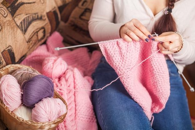 La donna lavora a maglia abiti di lana
