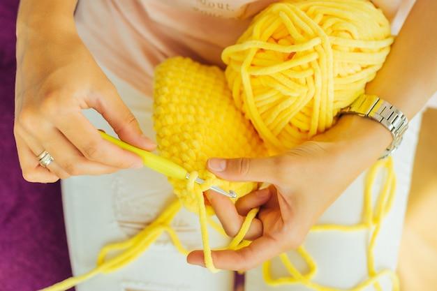 La donna lavora a maglia all'uncinetto. la ragazza si siede e lavora a maglia dal filato per maglieria.