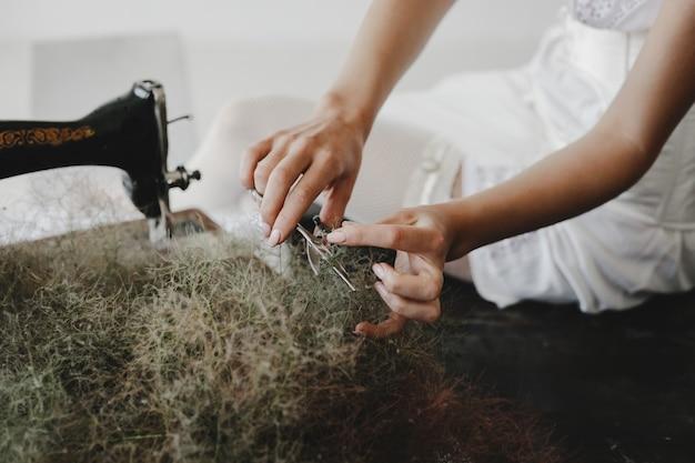 La donna lavora con la macchina per cucire seduto su un tavolo