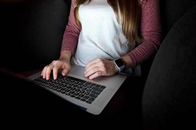 La donna lavora fino a tardi seduto sul divano con il portatile