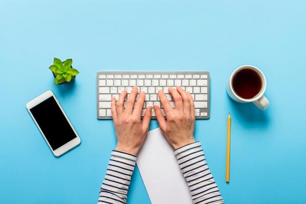 La donna lavora in ufficio su uno sfondo blu. concept area di lavoro, lavoro al computer, libero professionista