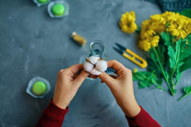 La donna lega il cotone al vaso per i fiori su un tavolo soppalcato