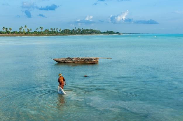La donna locale raccoglie le alghe nell'oceano sull'isola di zanzibar, sulla spiaggia di jambiani.