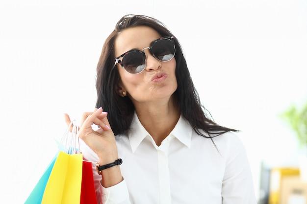 La donna lussuosa in occhiali da sole porta la spesa