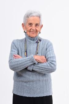 La donna maggiore con le braccia ha attraversato su priorità bassa bianca