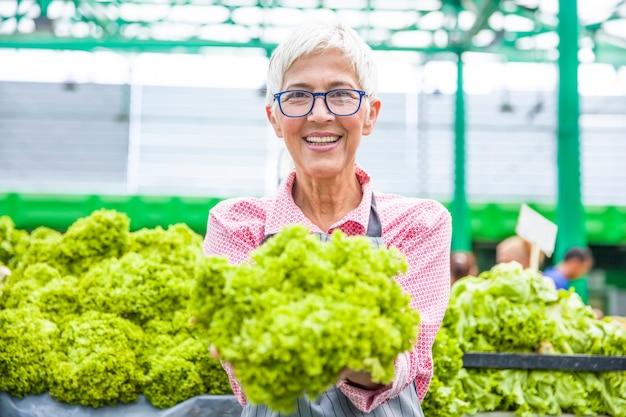 La donna maggiore vende la lattuga sul mercato