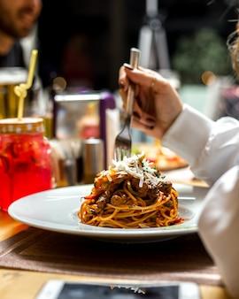 La donna mangia gli spaghetti della pasta con la vista laterale del parmigiano di verdi di carne