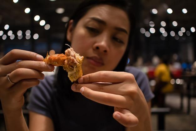 La donna mangia i gamberi al vapore con formaggio.